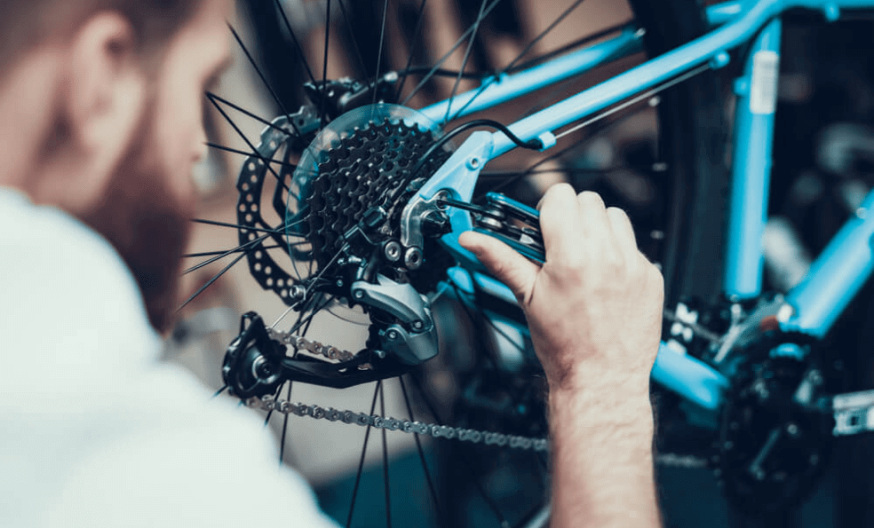 Bicycle mechanic working on a bicycle tire and spokes