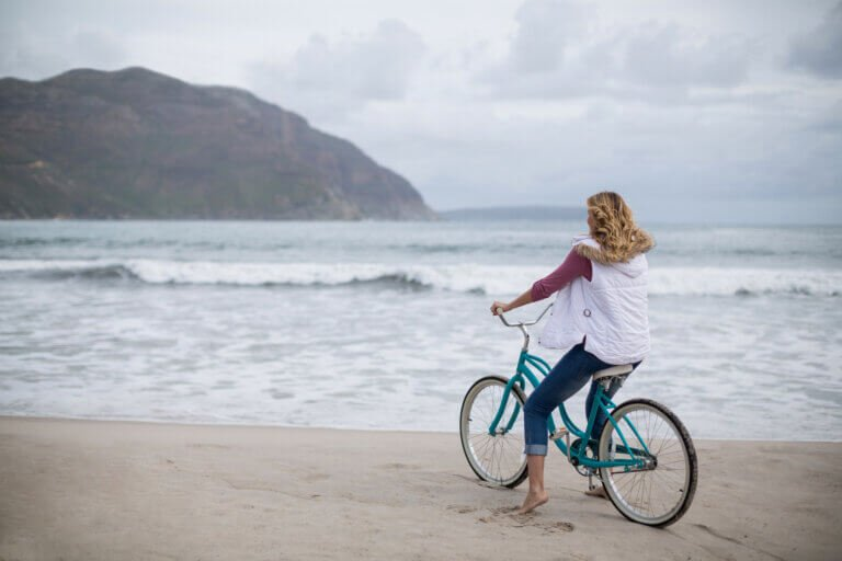 Woman riding her bicycle on the beach