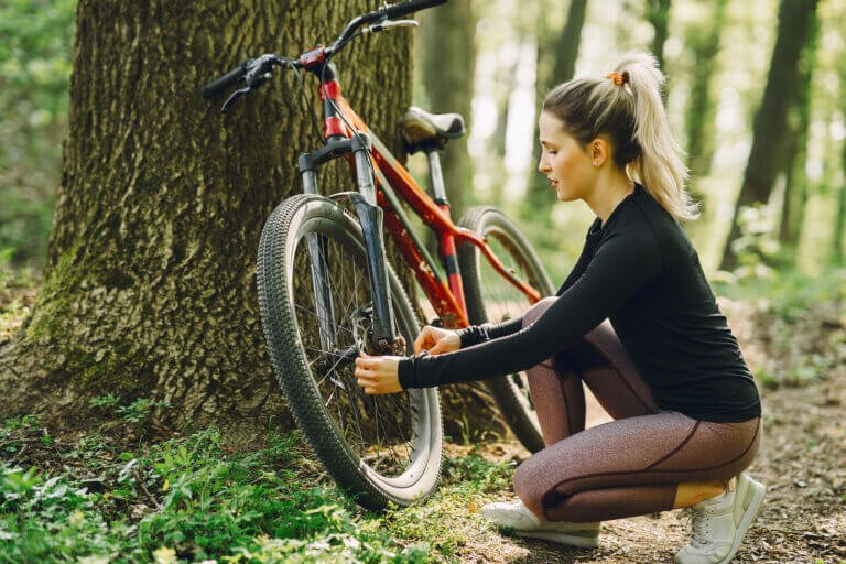 Woman with her mountain bike in the forest