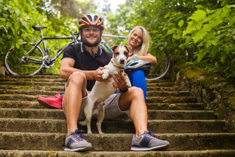Happy couple with dog sitting in front of their bicycles