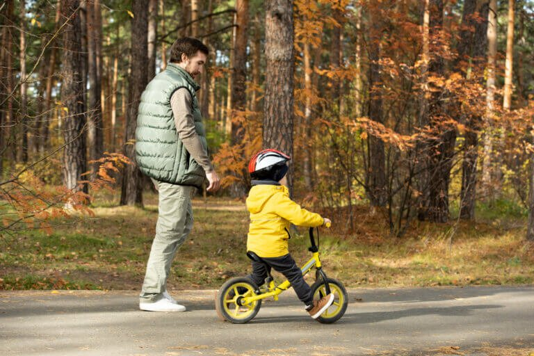 Young man walking by his little son in safety helmet and casualwear riding balance bicycle along wide road in park while enjoying chill at leisure